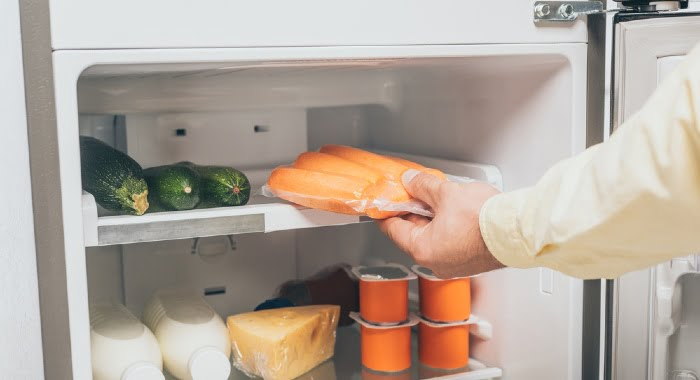 carrots in plastic bag being put in fridge